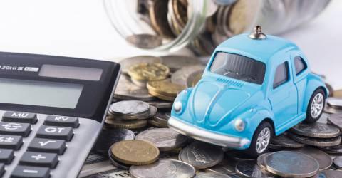 blauwe auto op stapel geld met rekenmachine
