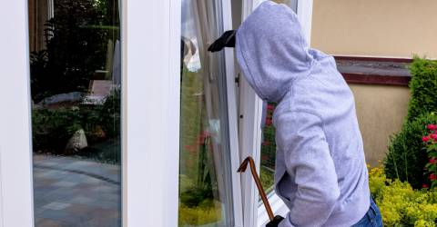 Een inbreker probeert in te breken in een open raam met een koevoet